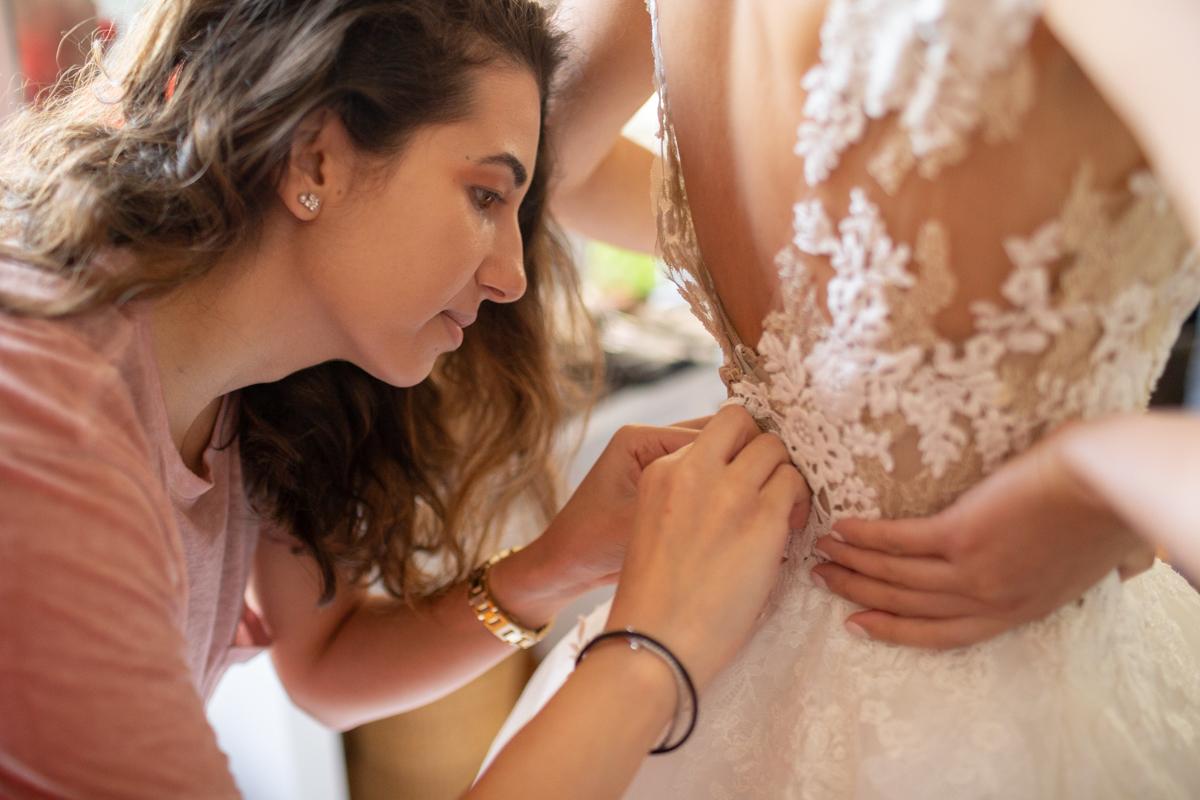 la témoin de la mariée boutonne sa robe