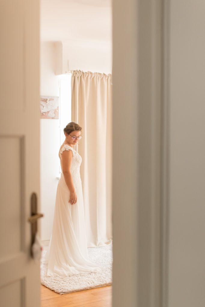 photo mariée avec sa robe a travers la porte