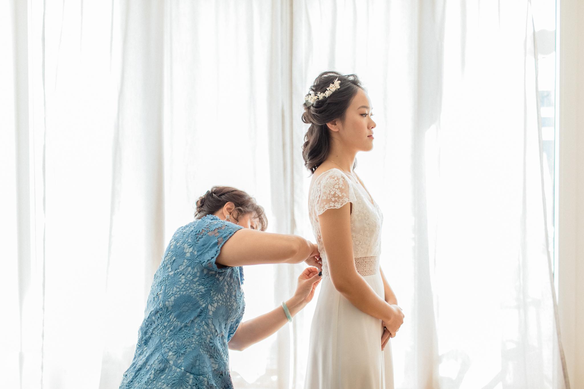 la mariée enfile sa robe avec l'aide de sa maman