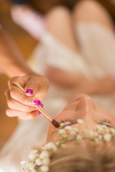 photo artistique des préparatifs de la mariée et de son maquillage avec sa mua prise de haut en plan serré sur ses cils